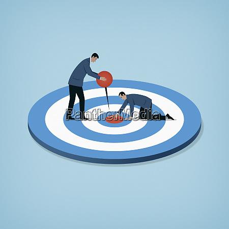 businessmen cooperating to hit target