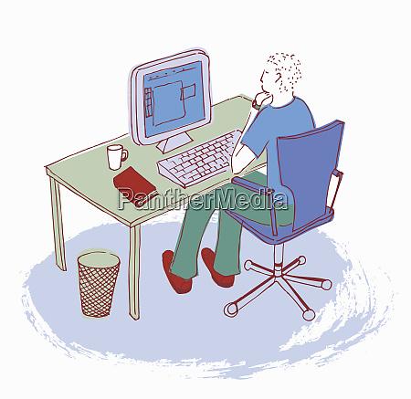 man working at desk using computer