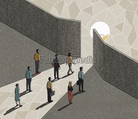 business people walking towards glowing light