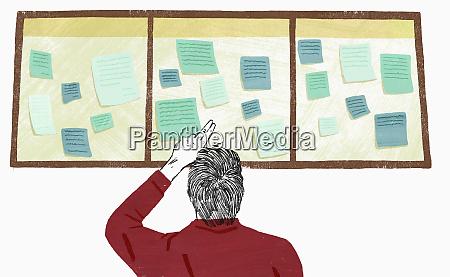man reading notices on notice board