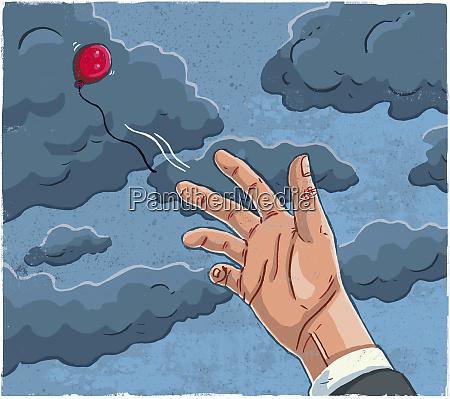 man releasing red balloon