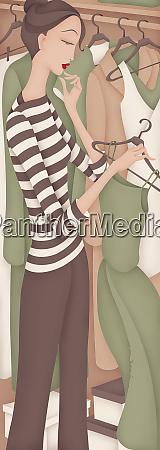 beautiful woman choosing dress from closet