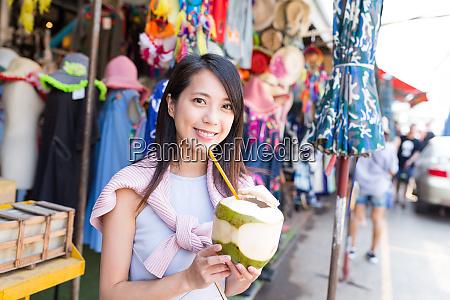 young woman enjoy coconut juicy in