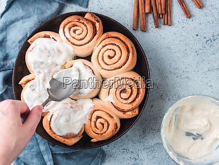 hand spreading frosting on cinnamon rolls