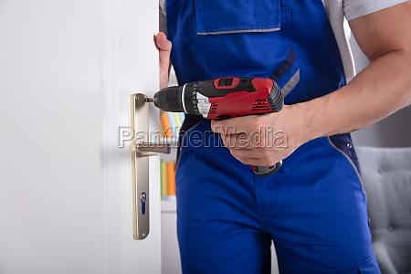 man installing door knob with wireless