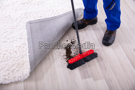 janitor cleaning dirt under the carpet