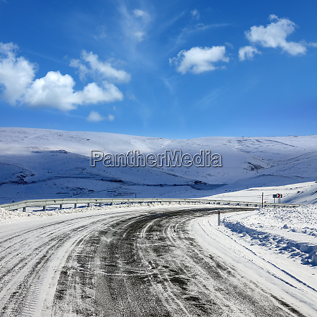 empty frozen asphalt road and snow