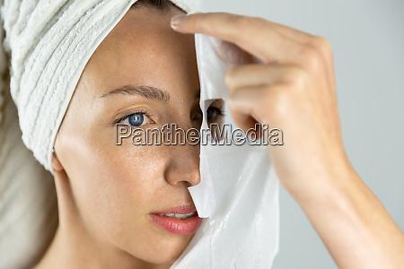 beautiful women applying facial mask with