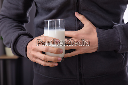 man having stomach pain holding glass
