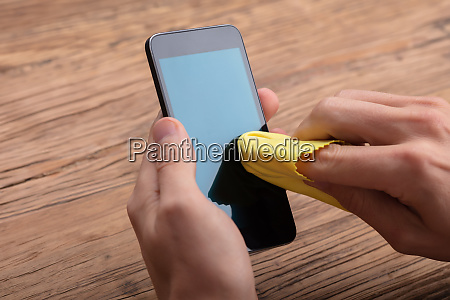 man cleaning mobile phone screen