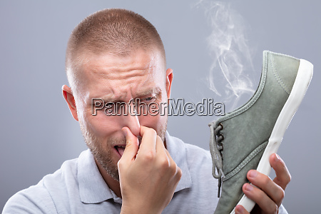 man covering his nose while holding