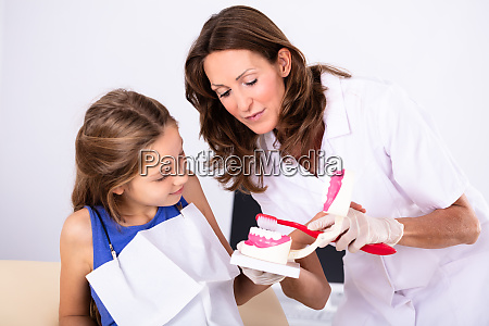 dentist teaching patient how to brush