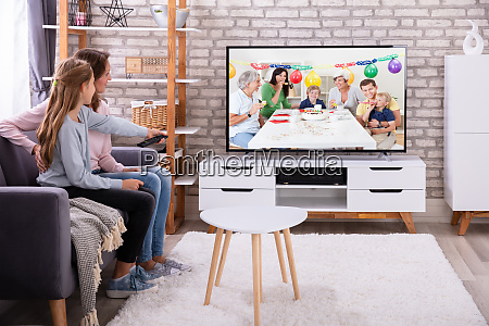 mother and daughter watching television in