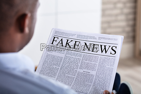 man reading fake news on newspaper
