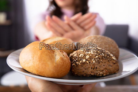 woman, refusing, bread, offered, by, person - 26052557