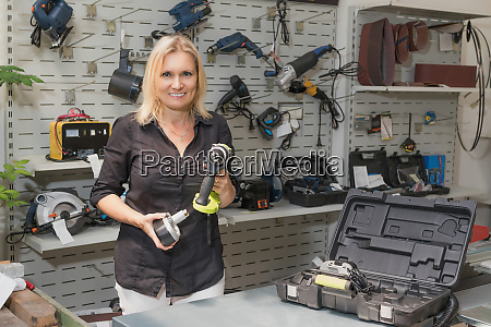 smiling saleswoman is selling a drill