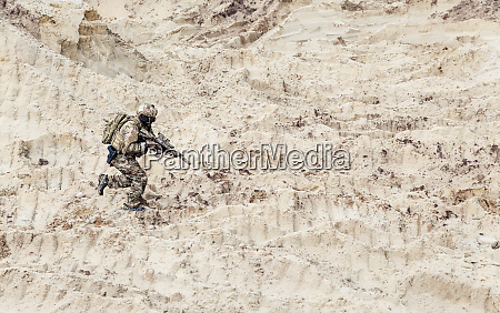 soldier with carbine running alone through