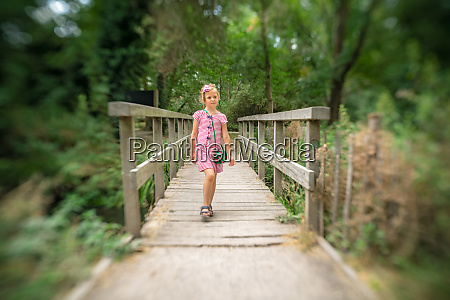 cute girl crossing wooden bridge