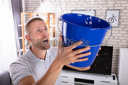 man holding bucket while water droplets