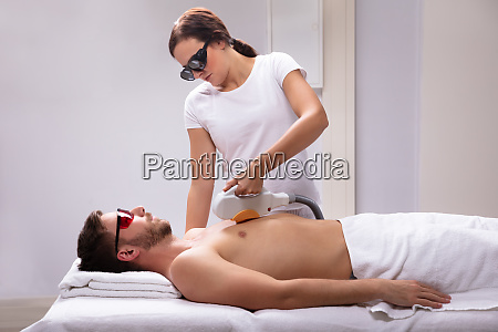beautician giving laser depilation treatment on