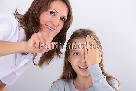 optometrist assisting girl while checking eyesight