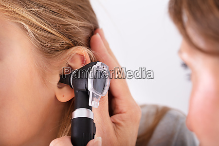 doctor checking girls ear