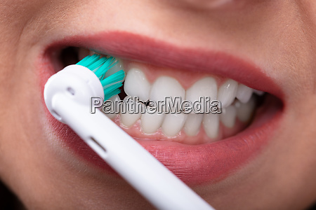woman brushing teeth with electric toothbrush