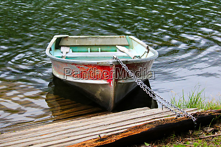 an aluminum row boat chained to