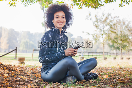 happy fitness afro woman listening music