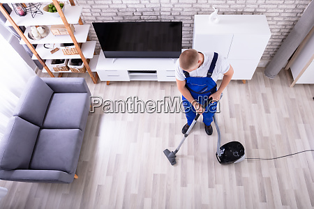 janitor cleaning floor with vacuum cleaner