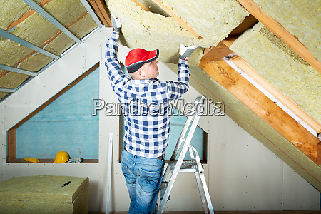 man installing thermal roof insulation layer