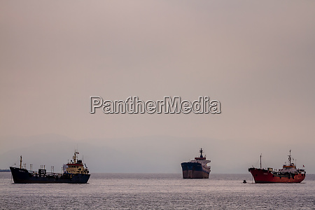 cargo ships anchored off shore in
