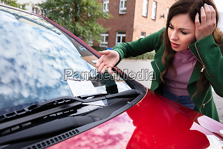 woman looking at ticket fine for