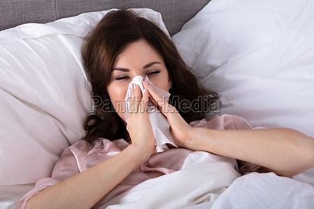 sick woman sneezing in handkerchief