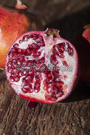 three pomegranades on dark wood