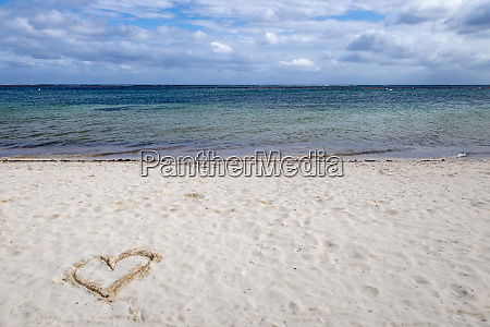 heart drawn in the sand of
