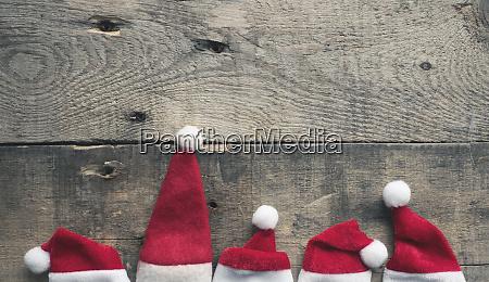 five hat of santa on wood