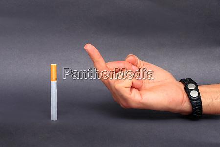 man holding cigarette between fingers