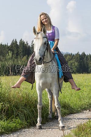 woman in dirndl rides on arabian