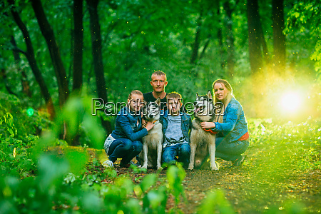 family with children and husky dogs