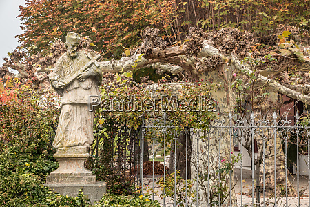 stone statue with colored leaves of