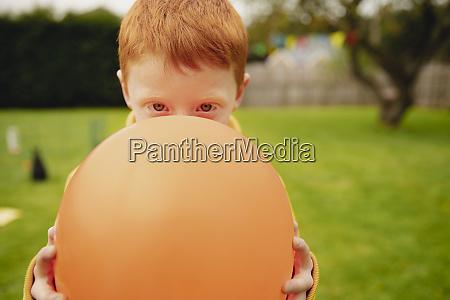 little boy peering over a balloon