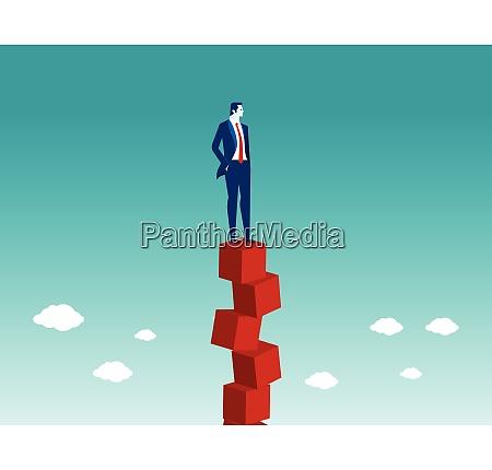 businessman balancing on red box