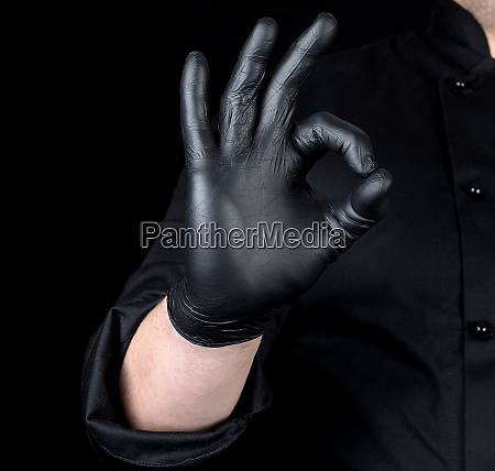 male chefs hand in black latex