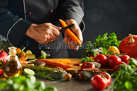 chef slicing fresh carrots for a