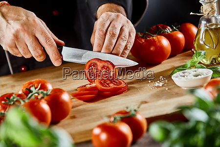 chef slicing fresh tomato for a