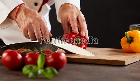 male chef cutting fresh capsicum or