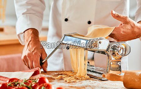 chef cutting fresh homemade pasta noodles