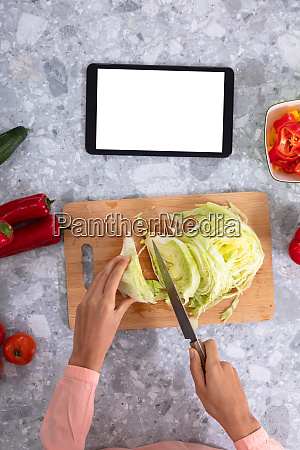 womans hand cutting cabbage with kitchen