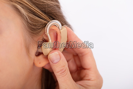 doctor inserting hearing aid in girls